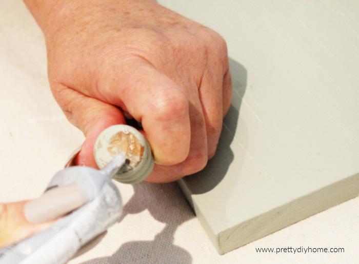 Adding E 6000 glue to wood legs while making a DIY table riser for farmhouse decor.