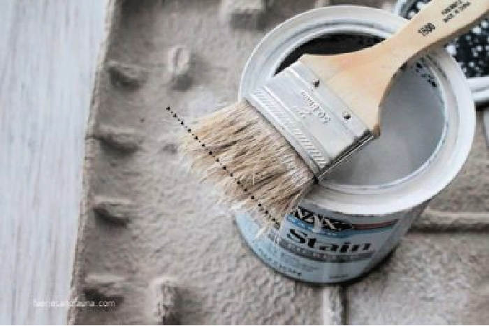 A dollar store chippy brush laying over a can of stain while refinishing a coffee table.