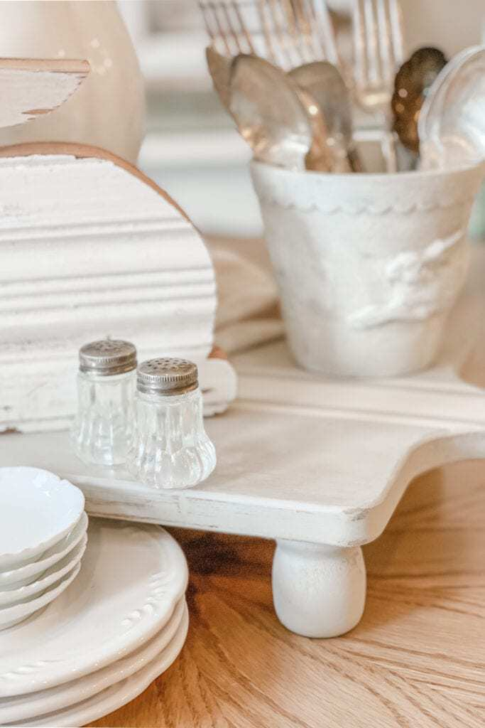 White DIY Cutting Board Riser made using a purchased cutting board. The table riser is white with a chipped finish and has a salt and pepper shaker as well as a plant pot full of silverware sitting on it