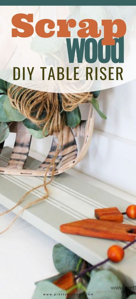 A DIY scrap wood table riser painted a soft green with white grain stripes. It is decorated with farmhouse decor and vintage wood accessories.