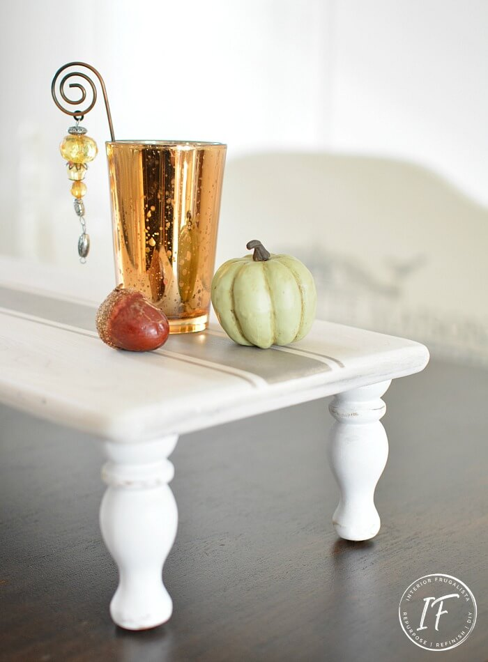 A DIY farmhouse table riser in white with long legs. It has a candle and pumpkins on top.