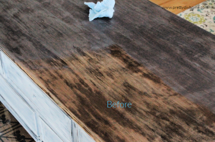 Adding stain and then wiping it off on a coffee table greige refinish project.