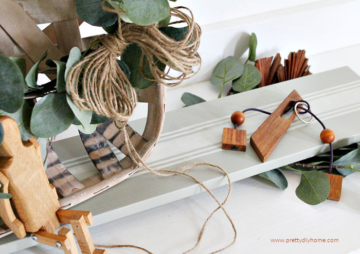 DIY table riser for farmhouse decor in soft green with ivory grain sack stripes. The table riser is displaying antique wood toys that were purchased at a garage sale.