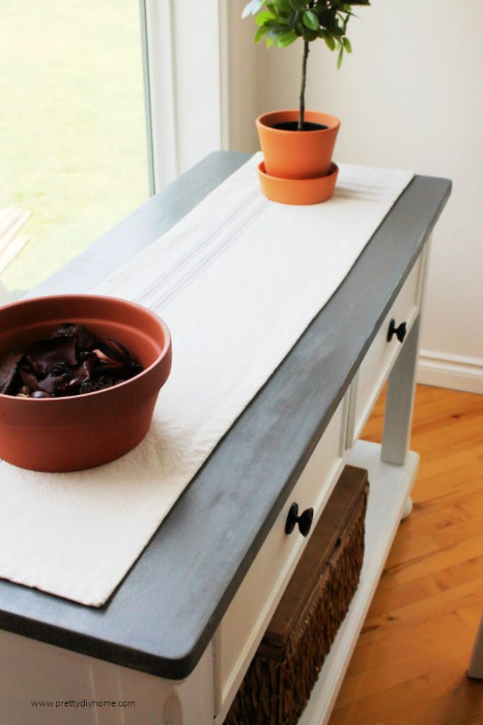 A refinished hallway table with a greige top and white painted sides. The table has a farmhouse runner on top.