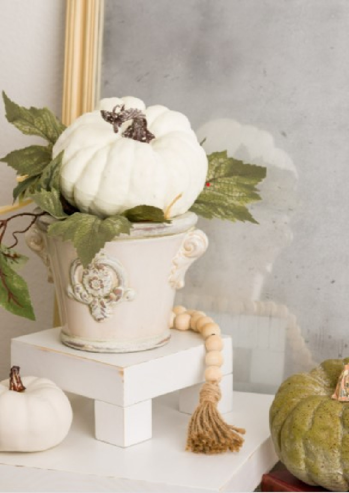 A handmade wood table riser with a farmhouse beads and green and white pumpkins