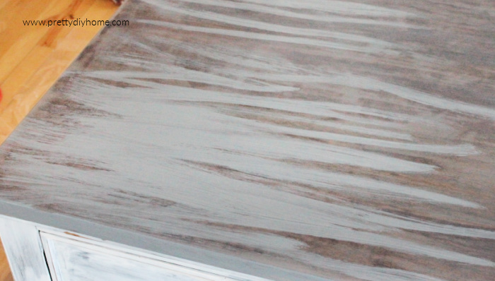 Adding strokes of gray stain to a coffee table top.