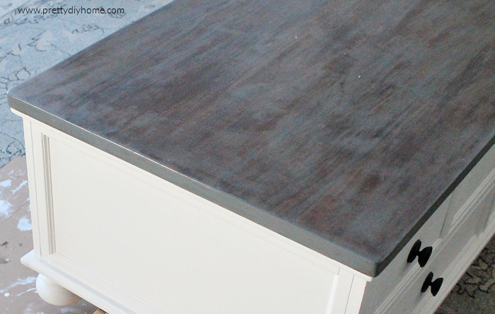 Refinished greige restoration hardware look finish on a refinished coffee table with white sides.