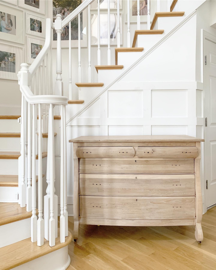 A beautiful lime wax glazed antique dresser surrounded by a white bannister. The dresser has been made over with the veneer removed.