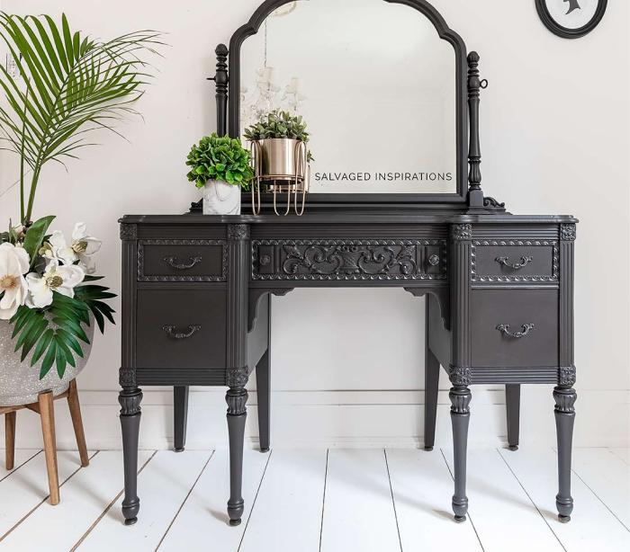 Dark coffee bean painted and refinished vintage vanity table with a mirror. It has no chair and is surrounded by pretty green plants.