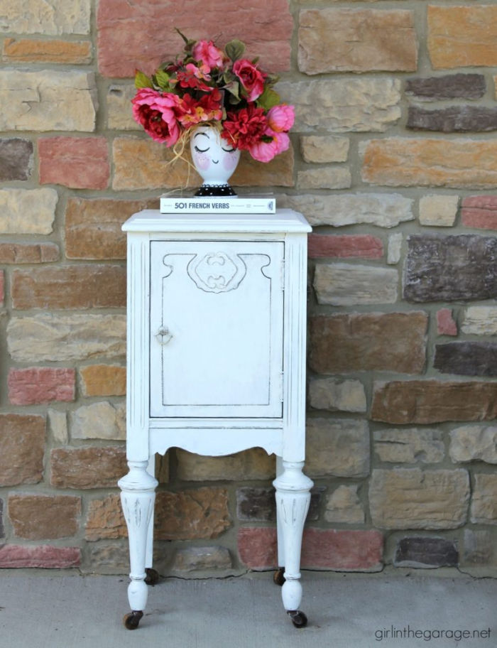 Nightstand in white paint that had damaged veneer.  The nightstand has pretty scrolling on the front door.